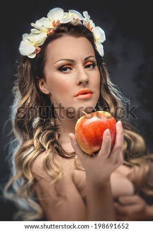 Beautiful seductive woman with apple, conceptual photo - stock photo