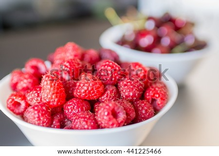 Beautiful selection of freshly picked ripe red raspberries in the white bowl with cherries in background - stock photo