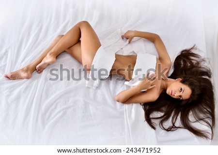 beautiful seminude woman with long hair laying on the white bed