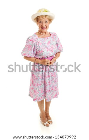 Beautiful senior lady from the Southern US, dressed in a party dress and hat.  Full body isolated on white.