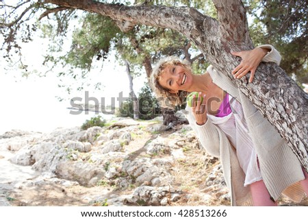 Beautiful senior tourist woman relaxing on coastal destination, being playful around tree trunk, eating green apple on holiday, nature outdoors. Healthy eating lifestyle, mature woman, sea exterior. - stock photo
