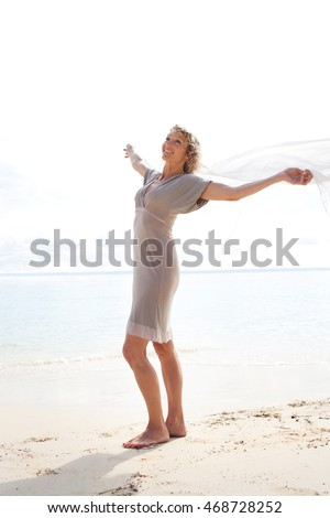 Beautiful senior tourist woman standing on destination beach whore with blue sea, holding floating fabric, smiling joyful, sunny outdoors. Healthy aspirational travel lifestyle.
