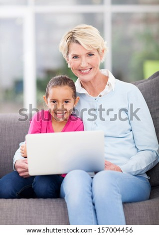 beautiful senior woman and her granddaughter using laptop computer at home - stock photo