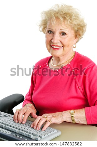 Beautiful senior woman typing on a desktop computer keyboard.  White background.
