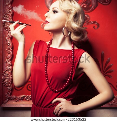Beautiful sensual blonde smoking a cigarette in red vintage room. Professional make up and hairstyle. Retro and vintage. Toned image. - stock photo
