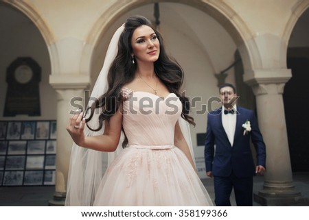 Beautiful sensual brunette bride in creamy wedding dress posing in front of church with groom in the background - stock photo