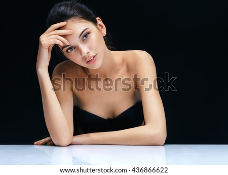 Beautiful sensual brunette girl. Close up of an attractive girl of European appearance on dark background. Skin care concept - stock photo