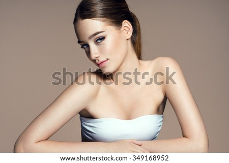 Beautiful sensual woman face looks at camera, skin care concept / photo composition of brunette girl on beige background - stock photo