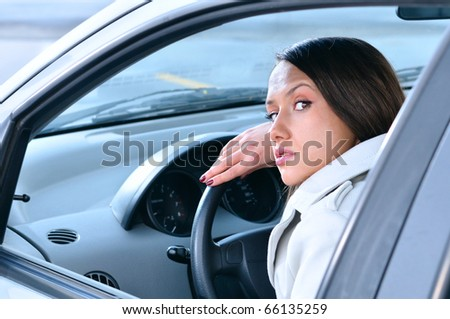 beautiful sensual woman put her head on steering wheel and looking back at camera - stock photo