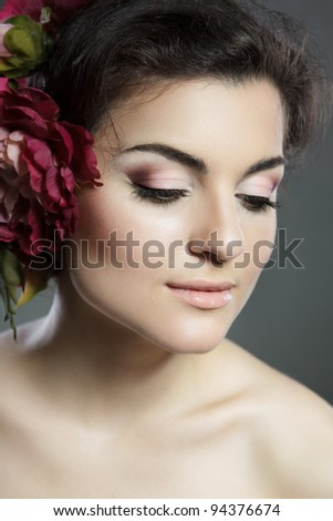 beautiful sensual woman with flowers in hair over grey background
