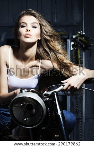 Beautiful sensual young girl in white vest sitting on old fashioned motorcycle in garage on grey wooden wall background, vertical picture - stock photo