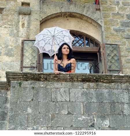 Beautiful sensual young girl with white umbrella standing on the stone balcony of the old medieval castle near open window, Tuscan, Italy - stock photo