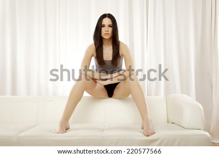 Beautiful sensuality and attractive sexy female young adult brunette woman posing in grey shirt on the white sofa - stock photo