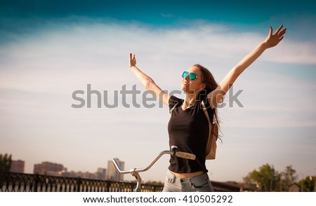 Beautiful sensuality elegance brown hair woman cyclist, has happy fun cheerful smiling face, black t-shirt, blue jeans. Has slim sport body. Motion on great bike in urban city. Portrait nature - stock photo
