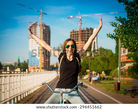 beautiful sensuality elegance brown hair woman happy fun cheerful smiling blue sunglasses black t-shirt jeans bicycle urban city portrait nature slim sport body hobby equipment riding bike cyclist  - stock photo