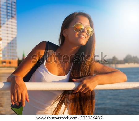 Beautiful sensuality elegance brunette woman, has happy fun cheerful smiling face, white t-shirt, slim sport tan body. Portrait nature urban city. Sunny megalopolis - stock photo