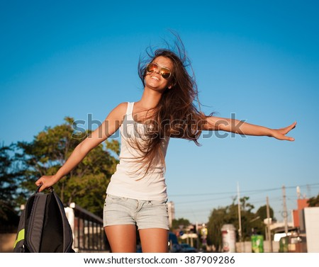 Beautiful sensuality elegance brunette woman, has happy fun cheerful smiling face, white t-shirt, blue jeans shorts, slim sport tan body, long hair. Portrait nature urban city. Sunny day. - stock photo