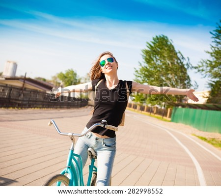 beautiful sensuality elegance haired hair woman happy fun cheerful smiling blue sunglasses black t-shirt jeans bicycle urban city portrait nature slim sport body hobby equipment riding bike cyclist  - stock photo