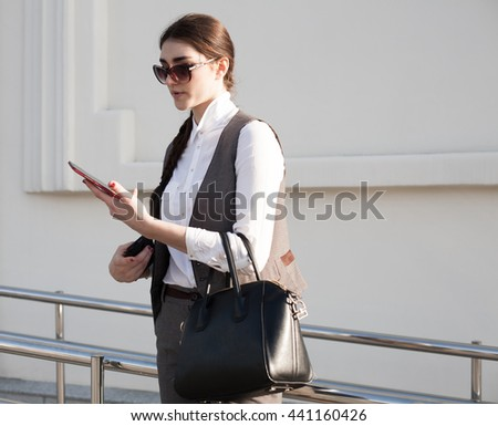 Beautiful sensuality elegance lady brunette woman, has cute face, dressed in gray business suit, white blouse, sunglasses, holding black leather handbag. Urban city portrait. Lifestyle background.  - stock photo