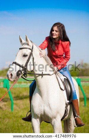 Beautiful sensuality elegance woman cowgirl, riding a white horse. Clothed blue jeans, red leather jacket. Has slim sport body. Portrait nature. People and animals. Equestrian. American ranch.