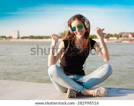 beautiful sensuality haired hair woman happy fun cheerful smiling blue sunglasses black t-shirt jeans music headphones river urban city portrait nature slim body technology device space impressions - stock photo