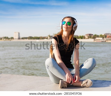 beautiful sensuality lady haired woman happy fun cheerful smiling blue sunglasses black t-shirt jeans music headphones river urban city portrait nature slim body technology device space impressions - stock photo