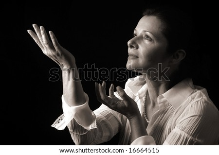 Beautiful serene woman looking up to heavenly light, sepia toned - stock photo