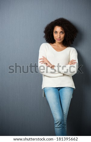 Beautiful serious African American woman leaning against a dark background with crossed legs and folded arms looking at the camera with copyspace and vignetting - stock photo