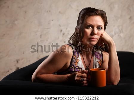 Beautiful serious European brunette female with coffee mug - stock photo