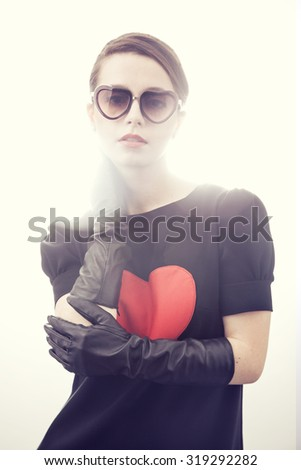 Beautiful serious young woman in sunglasses holding her hand on white background. Attractive girl at the classic image of 60s. Sexy brunette woman in retro style looking like Audrey Hepburn.Red heart - stock photo