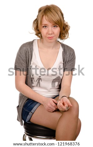 Beautiful serious young woman with curly blonde hair sitting on a stool looking at the camera isolated on white - stock photo