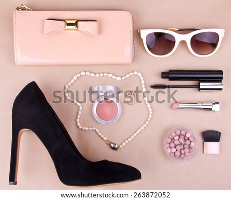 beautiful set of women's fashion accessories and cosmetics on a beige background - stock photo