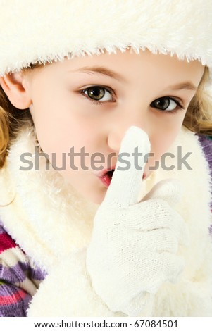 Beautiful seven year old girl dressed for winter with hat and gloves and scarf making quiet or secret gesture with hands. - stock photo