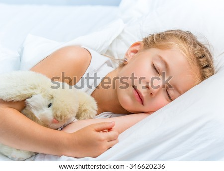 Beautiful seven year old girl sleeping in white bed - stock photo
