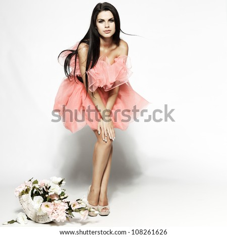Beautiful sexual brunette in pink clothes with the basket of flowers - stock photo