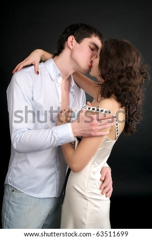 Beautiful sexual couple kissing over black background - stock photo