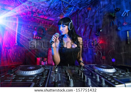 Beautiful sexual DJ girl working on a party in the old garage. - stock photo