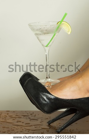 Beautiful sexual female feet in black leather shoes on high heels and cocktail with lime in glass on white background, vertical picture - stock photo