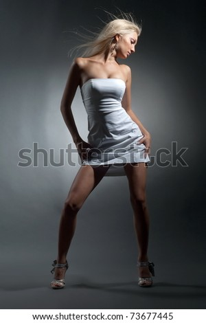 Beautiful sexual girl blonde pose on gray background - stock photo