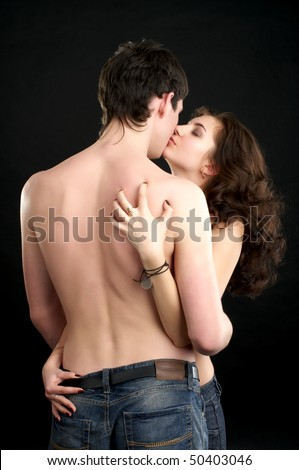 Beautiful sexual naked couple kissing over black background. - stock photo