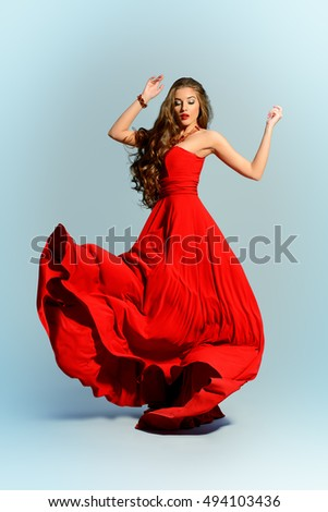 Beautiful sexual woman in red evening dress posing in motion. Fashion shot at studio.