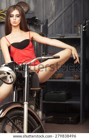 Beautiful sexual young girl with bright make up in red dress looking forward sitting on old motorbike in garage on workshop background, vertical picture - stock photo