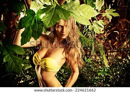 Beautiful sexual young woman in bikini in the rainforest. Vacation. Tropics. - stock photo