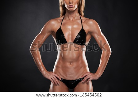 Beautiful sexy blond bodybuilder woman  lifting hands up. Standing isolated on black background