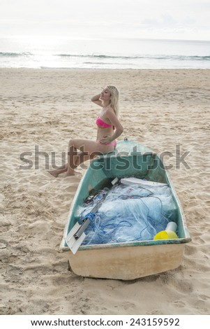 Beautiful sexy blond girl in pink bathing suit sitting alone on wooden plastic Cute woman near old boat on sand tropical beach against water texture and blue sky with sun set on background  - stock photo