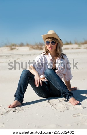 Beautiful sexy blond girl sitting on the sand