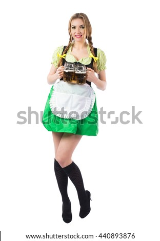 Beautiful sexy blond girl waitress Oktoberfest in Bavarian traditional dress with a glass of beer isolated on white background.