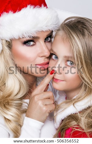 Beautiful sexy blonde female model mother and daughter dressed as Santa Claus in a red cap with at the White fur lovely makeup in Christmas time