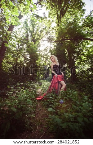 Beautiful sexy blonde girl in a black corset and long red skirt with a train - stock photo