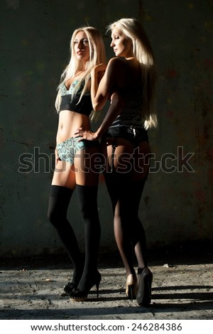 Beautiful sexy blonde girl posing in an old building collapsed - stock photo